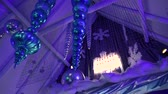 strop : Shimmering decoration during xmas party. Low angle footage of shiny Christmas decorations hanging from a vaulted ceiling. Stylish baubles and chandeliers hung from rafters indoors.
