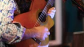 confortable : Guitarist plays to bar patrons by night. A jazz musician is viewed close up playing a vintage guitar on a small stage in a local bar Hands are seen plucking strings as he sways to music. Vidéos Libres De Droits