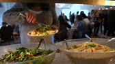 pohostinství : Corporate event professional catering. A bustling hall filled with chattering people is seen in the background as a woman fills her plate with healthy salads from a food display stand during event.