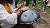 wróżby : Diverse people enjoy spiritual gathering A shamanic musician is seen up close, playing a metal handpan drum with hands during a multicultural festival in a sacred forest clearing with barefooted people Wideo