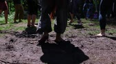 Diverse people enjoy spiritual gathering A group of barefooted people from all backgrounds come together in nature to celebrate native and traditional cultures, dancing barefooted on mud in slow motion Стоковые видеозаписи