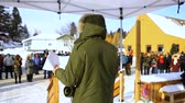 demonstrar : An over the shoulder view of an environmentalist giving a speech on climate change during a demonstration in a snowy town. Onlookers are seen in the background.