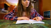 una persona : Young woman wearing checkered shirt is reading a book at her dining table. Fixed low angle from the table