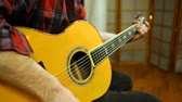 akustik : Wide, fixed scene, playing guitar with a pick