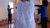 tanácsadás : Fixed angle of the back of a woman wearing a furry vest, doing exercise as part of a yoga class, with blurry people in a circle doing the same in the background Stock mozgókép