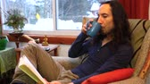 una persona : Young man with long hair and wearing cozy clothes is taking a sip of coffee while reading a book. Surrounded by windows at home. Traveling up