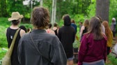 An intergenerational group of people are seen from the rear in slow motion, all facing a spiritual guide in a forest clearing during a mindfulness retreat.