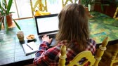 una persona : Girl wearing glasses and a checkered shirt is typing on her black keyboard with coffee and cookies by her side. Traveling up wide angle from the top left Archivo de Video