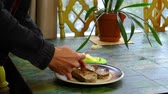 broodrooster : Young Man with black jacket is buttering two dark toasts made of homemade wholegrain bread. Traveling up