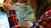broodrooster : Young woman with checkered shirt is eating a soup on a green ceramic table by the window. Closeup fixed angle scene
