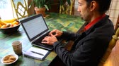 Young man wearing a black jacket and a red shirt is typing on a black laptop in his dining room. Traveling up from the left. Portrait view Стоковые видеозаписи