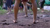 Closeup and slow motion footage on the naked legs and feet of a slim caucasian man, standing barefooted on mud as people enjoy sacred festival in woodland. Стоковые видеозаписи