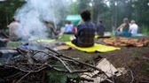 una persona : Rising smoke from kindling on a camp fire is seen close up in slow motion, setting the calm atmosphere during a group meditation and yoga session in nature.