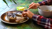 sessel : Young woman with checkered shirt is buttering dark toasted homemade bread to eat with her soup, on a green ceramic table by the window. Traveling up closeup Videos