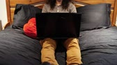 rosto humano : Straight view of a man with long hair looking disappointed or disgusted while looking at his laptop, sitting on his bed - traveling up Stock Footage