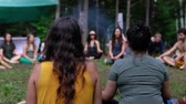 wróżby : A large group of people are seen sitting around a spiritual guide in a forest clearing as she teaches deep and mindful meditation at multicultural festival.