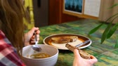Young woman with checkered shirt is eating a buttered toast and a soup on a green ceramic table by the window. Traveling up closeup scene
