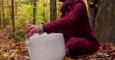 mistica : Fixed angle from the left side filmed in the forest and showing trees with leaves turned to yellow and dead leaves all around the white instruments. Man is wearing an urban red jacket.