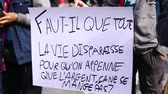 gösterici : two close up shots of environmental slogans on hand written placards at a climate demonstration in french language