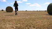 palheiro : A female photographer walks across a field of freshly cut grass and stops to shoot haystacks in the landscape. Clip is in slow motion from a low angle
