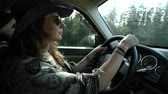 探検家 : Alternative woman with cowboy hat, sunglasses, tattoos and long wavy brown hair is driving on a country road seen in profile in slow motion 動画素材