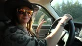 zigeuners : Woman with cowboy hat, sunglasses, tattoos and wavy brown hair is driving on a country road and moving to music in slow motion looking to camera