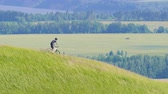 bike ride : the cyclist looks around and moves down from the green hill