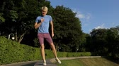 elegáns : Happy man dances on a half round curb protecting park in slo-mo