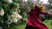 jaro : Smiling girl is spinning in a red dress near the lilac bushes in slow motion Dostupné videozáznamy