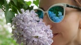 smród : Girl in sunglasses sniffs lilac close up