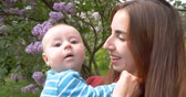 niania : 4K - Young mother kisses the baby in the park