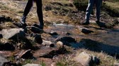 Slim female legs in boots crossing a mountain rill in the Carpathians in slo-mo