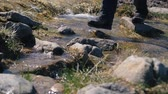 Small female feet in boots crossing a mountain rill in the Carpathians in slo-mo