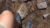Male legs in sneakers crossing a mountain runlet with stones in slow motion