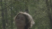 Middle aged woman shake her head in the forest - slow motion.