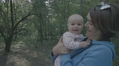 nesil : Happy family in the forest - mother kisses her baby in slow motion. Stok Video