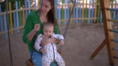 custodia : Smiling mom and little baby ride on a swing in slow motion