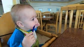 lekeli : A small child nibbles a spoon in the chair