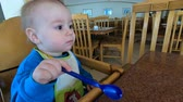 püré : Little baby licks the spoon in the highchair in slow motion