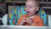 králíček : One year old baby sits in the kitchen and plays with an easter egg - slow motion Dostupné videozáznamy