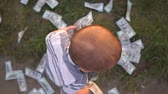 nape : Small boy throws hundred dollar bills around him in slow motion, view from above Stock Footage