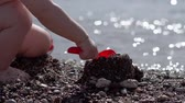 lopata : A small child digs the ground and builds a castle on the beach in slow motion