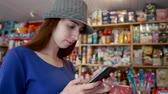 halenka : Stylish brown hair girl surfing the net on her phone in a small shop in slow motion
