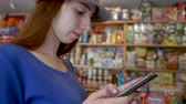 halenka : Smart brown hair girl browsing the net on her phone in a petite shop in slo-mo