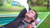 mentira : Cheery blond man lying on a wattled hammock smoking hooka in summer in slo-mo