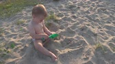 Little boy sits in the sand and plays with a bucket and a shovel. Wideo