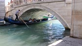 Tourist people having fun trip on gondola with gondolier sailing under bridge in Venice