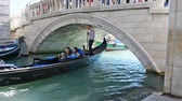венето : Tourist people having fun trip on gondola with gondolier sailing under bridge in Venice