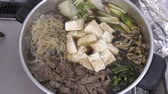 dining table : Sukiyaki hot pot during cooking with beef and various ingredients Stock Footage