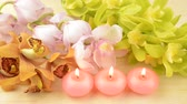 Three pink candles in front of three kind of orchid flowers on wood table